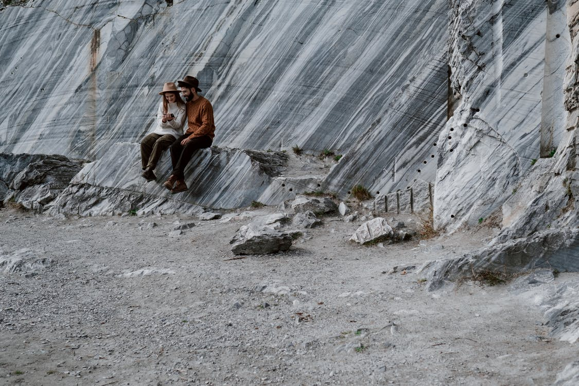 Man in Brown Jacket Sitting on Rock Near Waterfalls