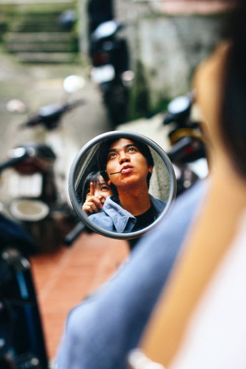 Reflection of young ethnic couple sitting on motorcycle while pointing and looking away