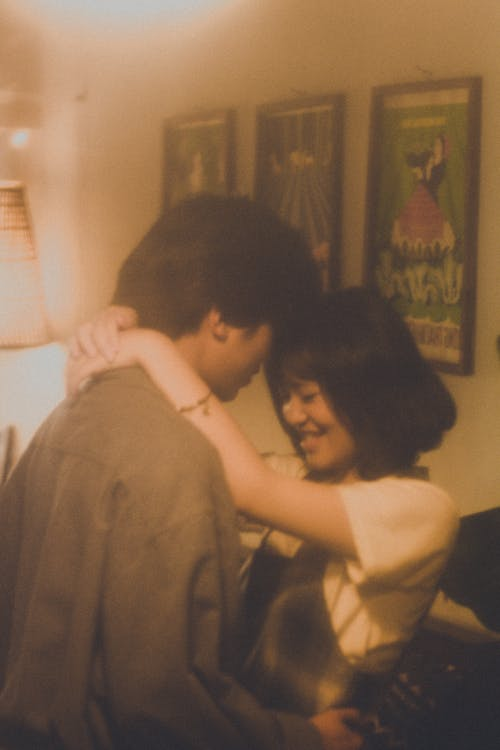 Asian couple hugging in room while standing