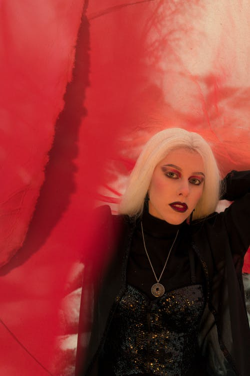 Serious young female with long white hair and dark makeup in Gothic styles outfit standing under red cloth and looking at camera
