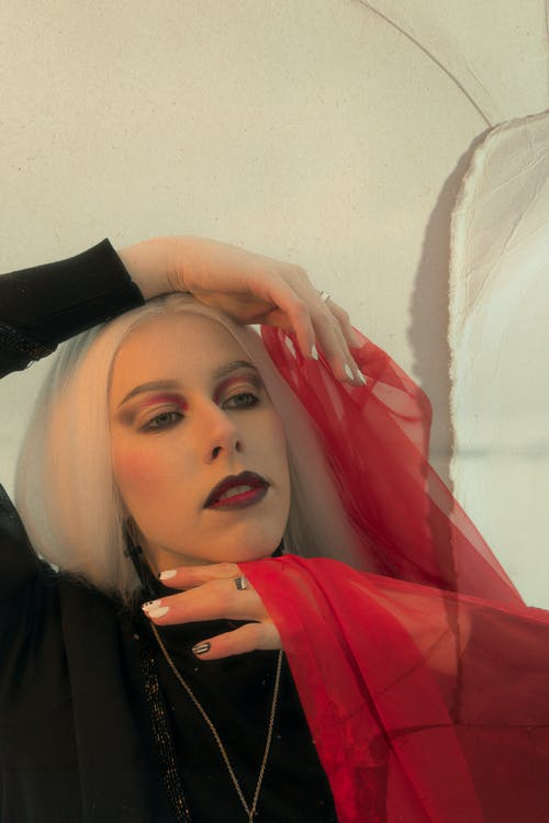 Stylish young female with long white hair and dark makeup touching face and looking away pensively while standing in studio with red veil in hands