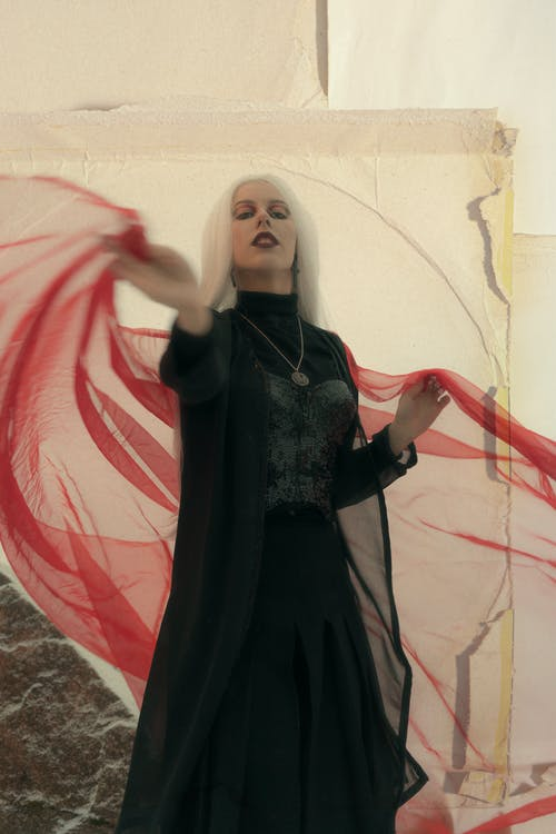 Self assured young Gothic female with long white hair in maxi black dress waving red veil and looking at camera against shabby wall