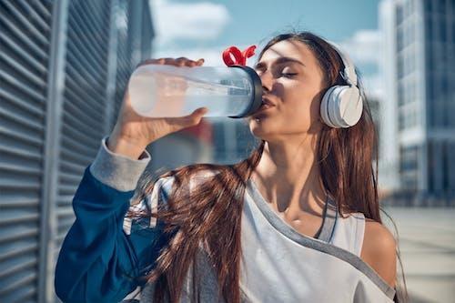 Kostnadsfri bild av dricka vatten, hörlurar, kvinna