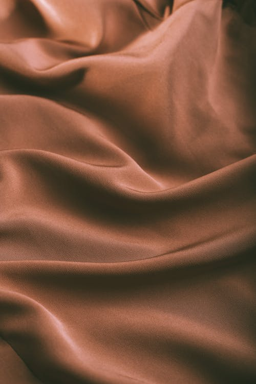 From above of elegant brown draped silk fabric with smooth texture as abstract background