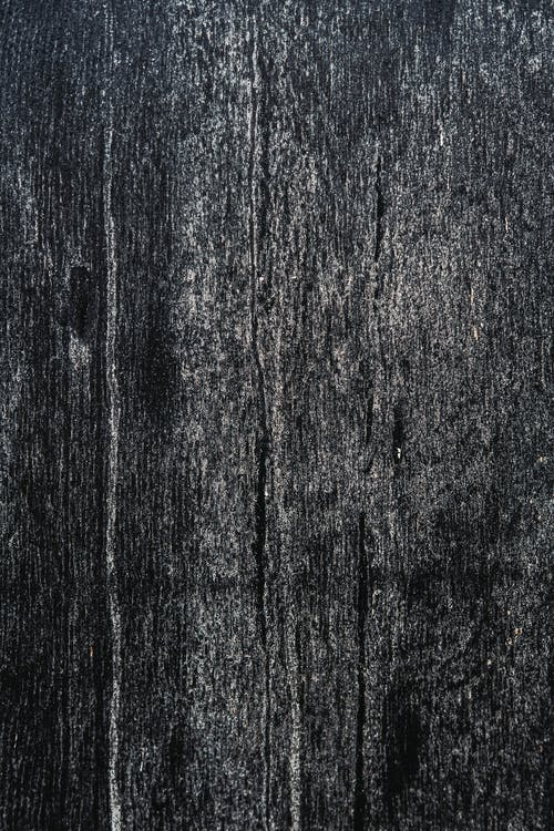 Black and white of textured background of wooden plank with uneven surface and scratches