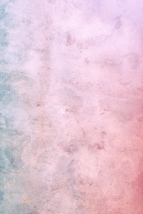 Pink and blue colored concrete weathered wall with uneven surface as abstract background