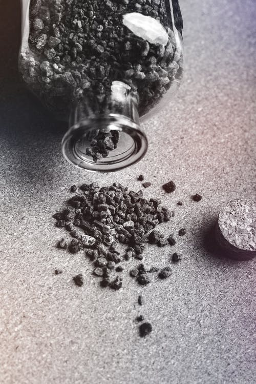 From above black and white of activated carbon granules scattered on table from glass jar with cork