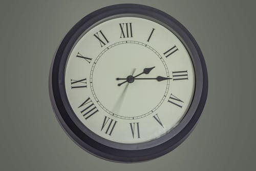 Round black mechanical clock with Roman numerals hanging on gray wall