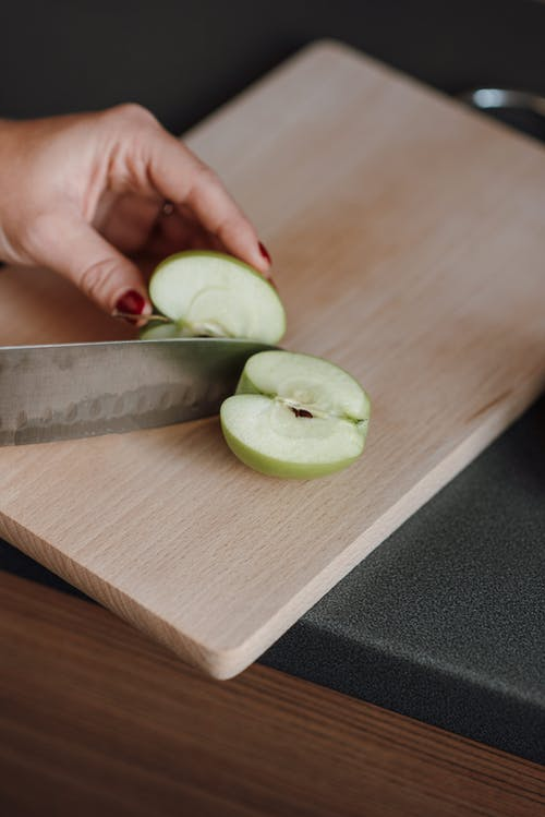 From above of crop faceless female cutting fresh juicy apple with sharp knife on wooden chopping board in kitchen
