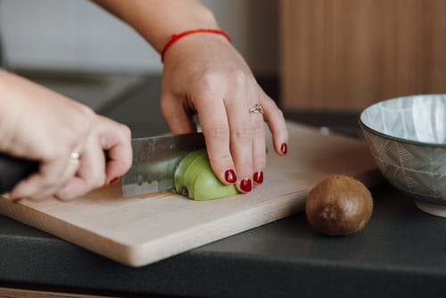 Crop anonymous female cutting ripe green apple on wooden cutting board in kitchen in daytime