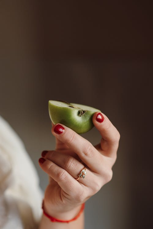 Female holding half of ripe apple