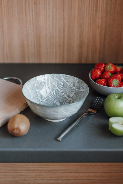 Empty bowl and cutting board placed on table near fresh apples and strawberries in kitchen in apartment