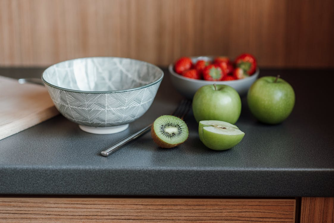 Kitchen counter with fruits and berries near dish and fork