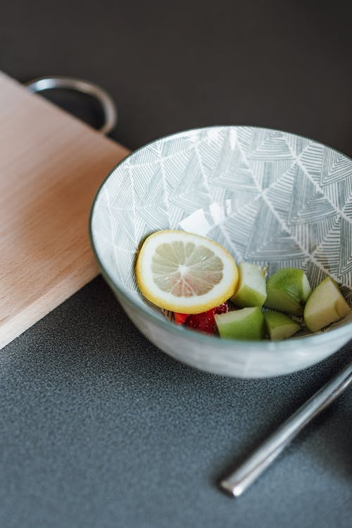 High angle of counter with wooden board and sliced lemon and apple served in colorful ceramic plate