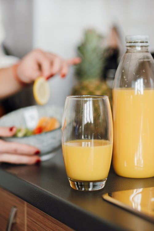 Glass and plastic bottle with natural fruit juice on table near bowl with salad against crop blurred lady having meal