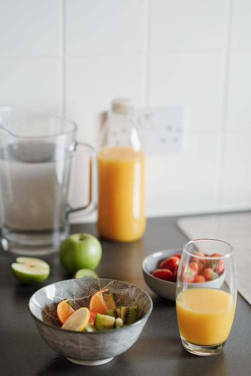 High angle of glass of fresh juice and bowls with fruit salad and small bowl with strawberries