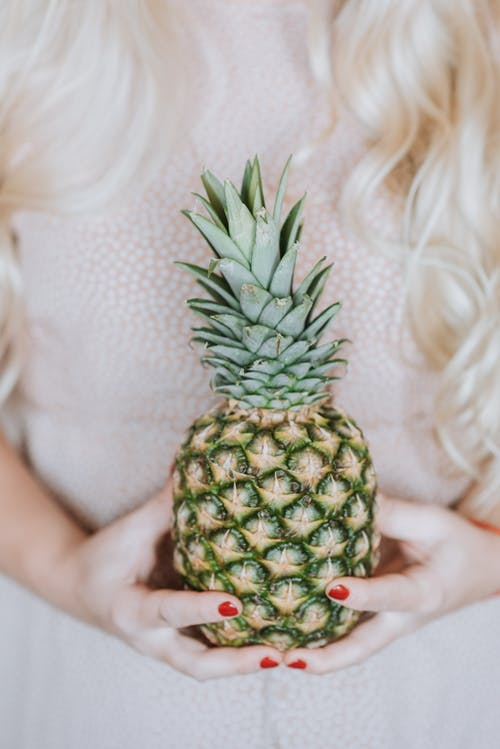 Unrecognizable female with long blond hair holding big fresh pine apple in hands