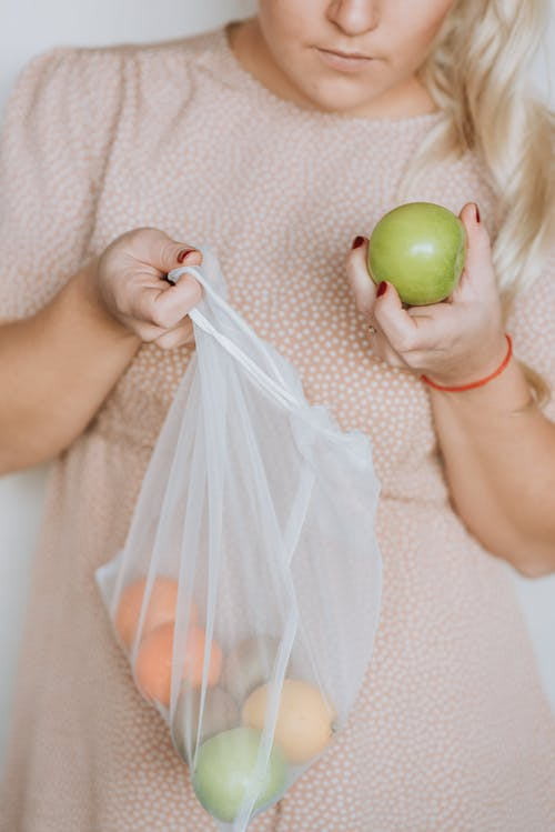 Woman with fresh fruit in eco sack