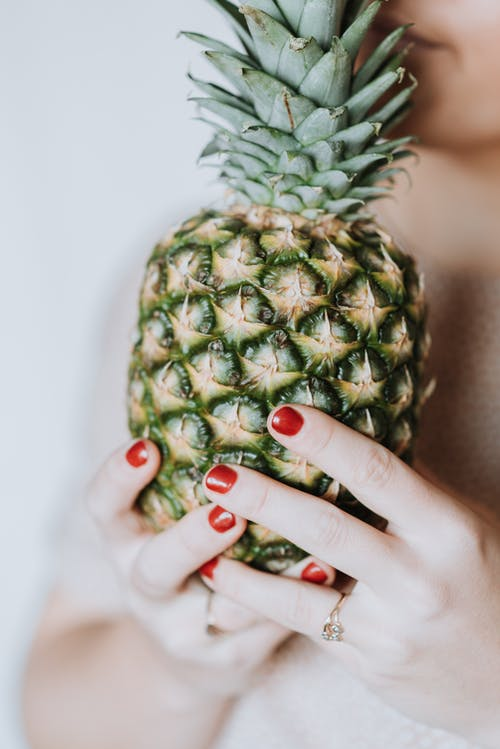 Unrecognizable woman holding in hands big pineapple and enjoying fresh aroma on grey background