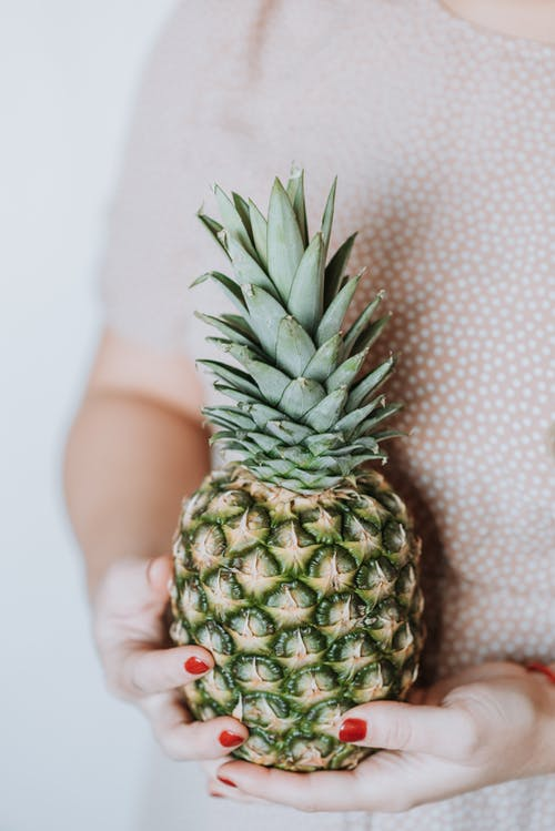 Unrecognizable woman in pink dress holding big ripe pineapple on grey background