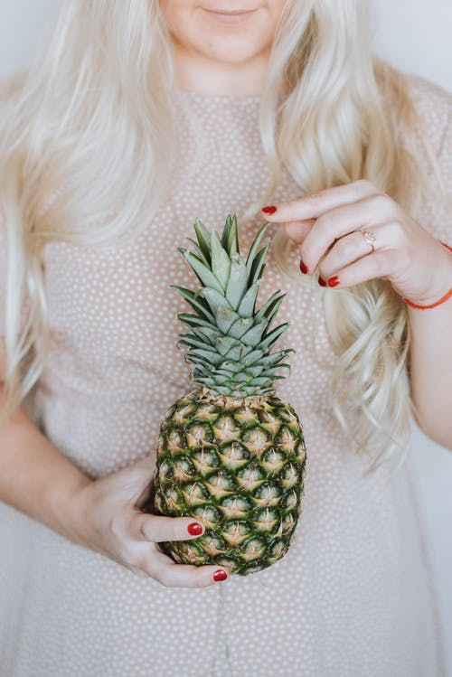 Unrecognizable long haired blond woman in pink dress holding ripe pineapple and touching spiky leaves
