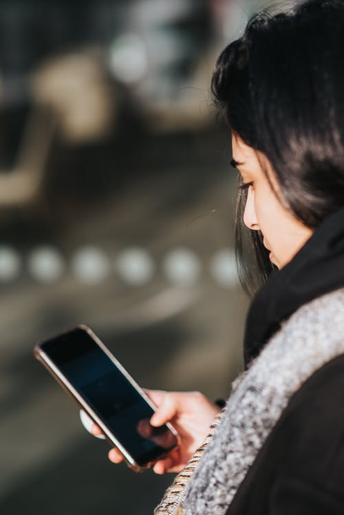 Woman using smartphone on city street