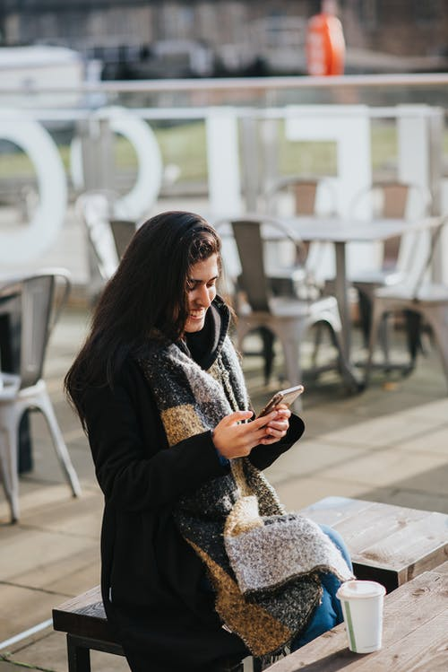 Young cheerful Hispanic female text messaging on cellphone at table with coffee to go in urban cafe
