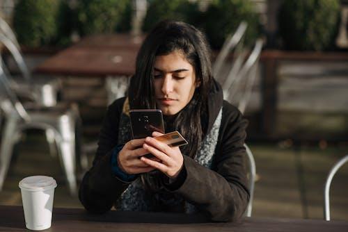 Vrouw In Grijs Jasje Met Bruine Smartphone