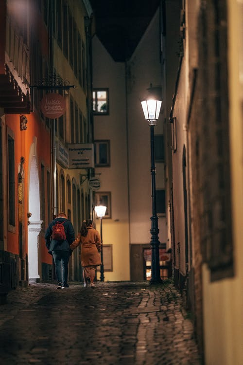 A Couple Walking In An Alley At Night