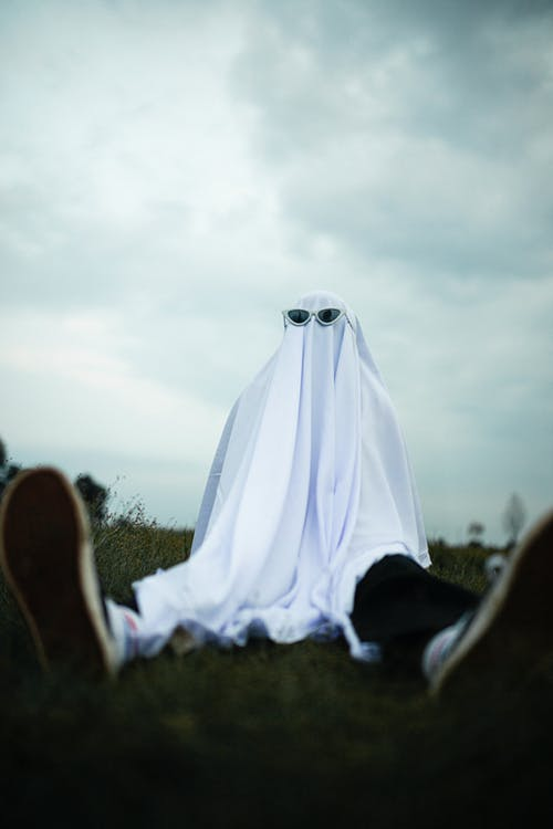 Child in ghost costume sitting in park