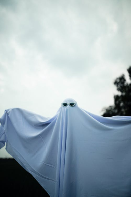 Little child playing scary ghost standing with raising hands