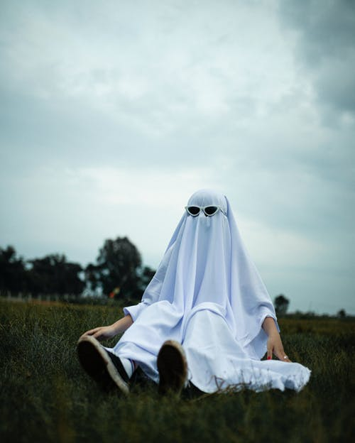 Low angle of child playing ghost in imaginary game and sitting on grass in park