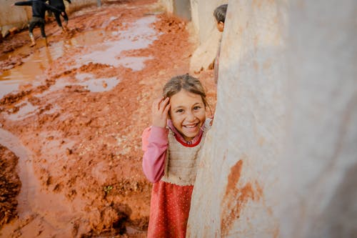High angle of cheerful girl touching hair and laughing while standing on mud in dirty settlement