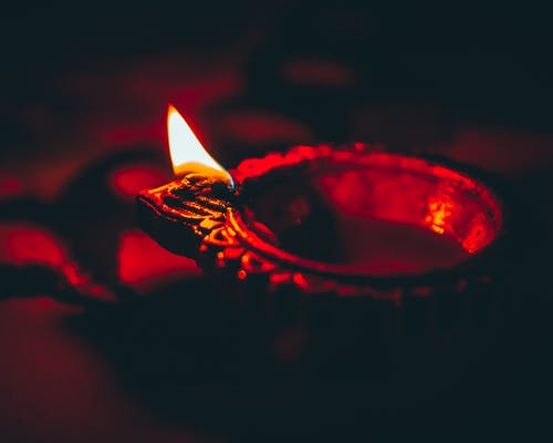 Diya burning on table in darkness