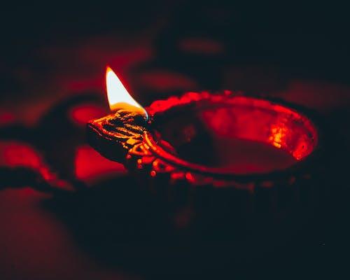 Diya burning on table in darkness