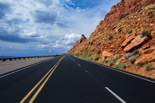 파란색과 흰색 맑은 흐린 하늘 아래 갈색 암석 사이의 회색 아스팔트 도로