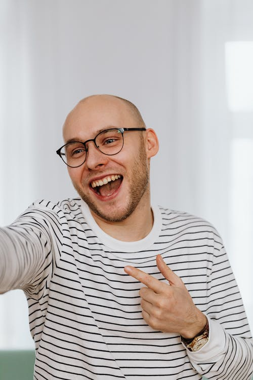 Man in Black and White Striped Shirt Laughing