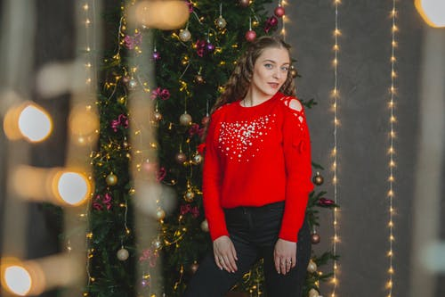 Content woman standing near Christmas tree