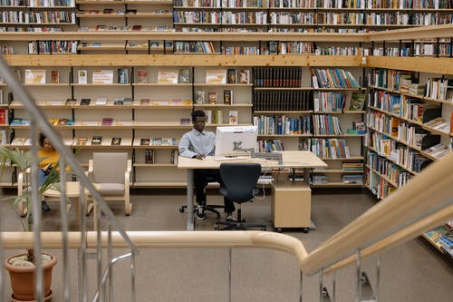 Photo Of Man Using Computer In Library