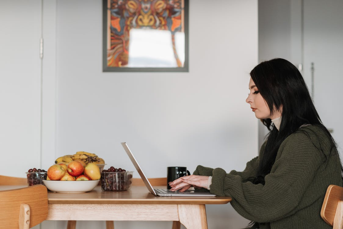 Freelancer typing on laptop at table with fresh fruits