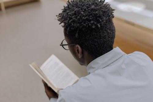 Man in White Dress Shirt Wearing Black Framed Eyeglasses Reading Book