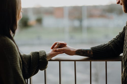 Crop smiling couple holding hands on balcony