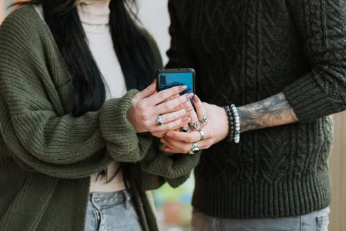 Crop anonymous tattooed man in accessories near girlfriend with cellphone spending time on weekend