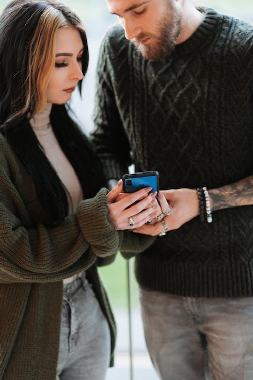 Mulher De Casaco De Lã Marrom Segurando Um Iphone Prateado 6