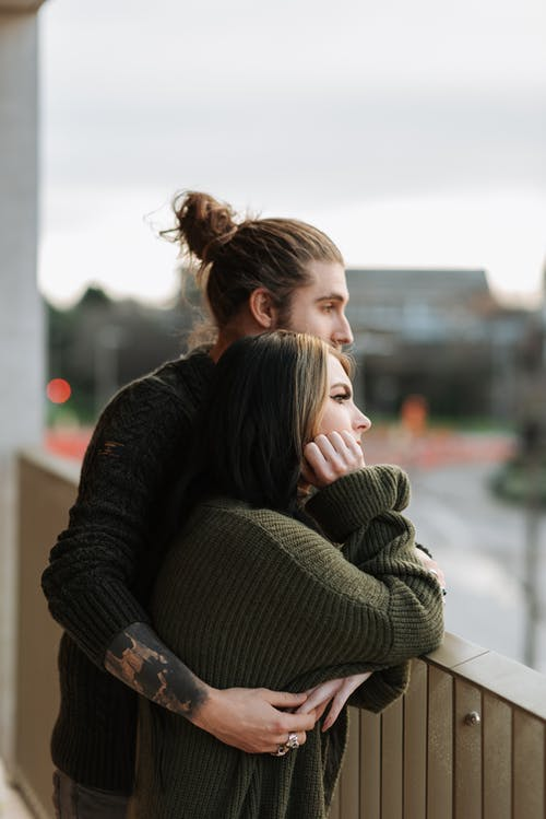 Side view of young hipster male embracing female beloved while admiring town from fenced balcony and looking away
