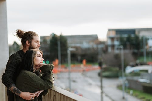 Side view of young unshaven male embracing female partner while admiring city from fenced balcony and looking away