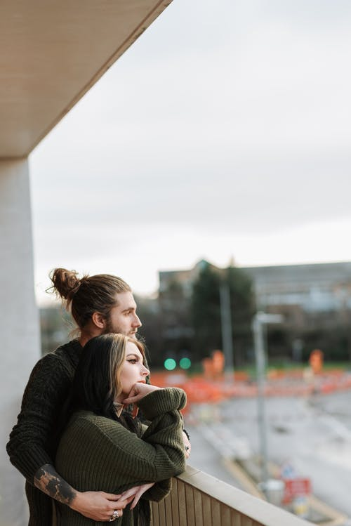 Side view of young hipster man embracing dreamy female partner while looking away on fenced balcony in city