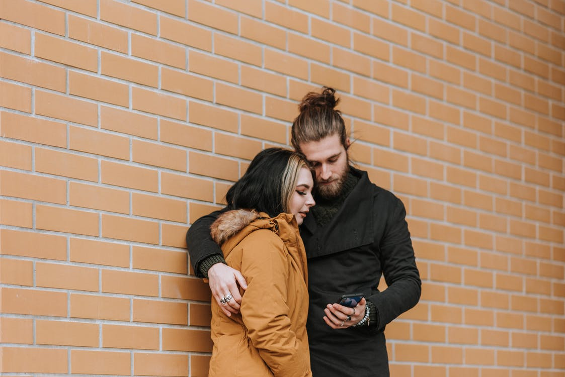Young unshaven man embracing female partner while surfing internet on cellphone near wall in daytime