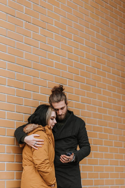 Young couple embracing and sharing smartphone near brick building