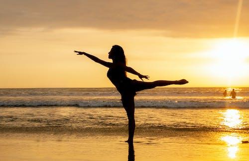 일몰시 해변에서 점프하는 여자의 실루엣